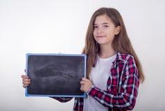 Молодой студент держа черную доску с пустым космосом и рекламирует что-то стоковые фото