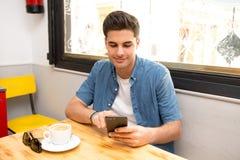 Молодой студент используя его умный телефон для того чтобы прочитать текст пока имеющ кофе стоковое изображение rf