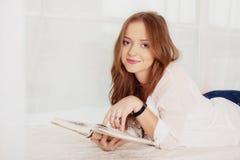 Молодой студент лежа и читая книгу Концепция отдыха a Стоковые Изображения RF