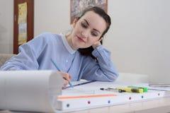 Молодой студент подготавливает архитектурноакустическую работу на таблице с белыми рисовальной бумагой и канцелярскими принадлежн Стоковая Фотография RF