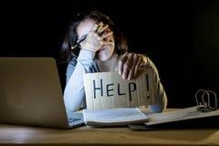 Молодой студент работая поздно на ноче на ее компьютере держа знак помощи стоковая фотография rf