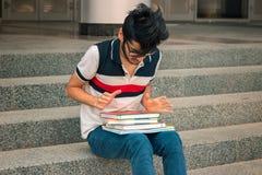 Молодой студент сидит на шагах и смотрит книги стоковое изображение
