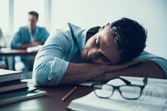 Молодой студент спать в классе на коллеже стоковая фотография