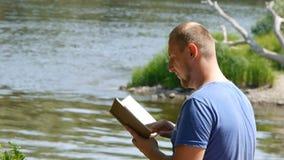 Молодой студент читает книгу на речном береге Турист с книгой в природе сток-видео