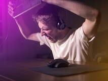 Молодой сумашедший шальной gamer ломая клавиатуру играя видеоигры на компьютере поздно в ноче стоковые изображения