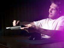 Молодой сумашедший шальной gamer ломая клавиатуру играя видеоигры на компьютере поздно в ноче стоковое изображение rf