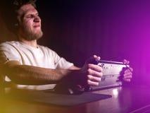 Молодой сумашедший шальной gamer ломая клавиатуру играя видеоигры на компьютере поздно в ноче стоковое фото