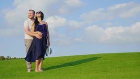 Молодой супруг нежно держит его беременную жену животом Стойка на красивом зеленом луге акции видеоматериалы