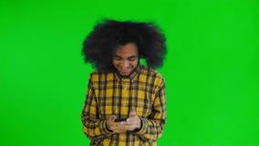 Молодой счастливый африканский бизнесмен используя телефон и получающ хорошие новости на зеленом экране или предпосылке chroma кл акции видеоматериалы