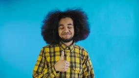Молодой счастливый афро американский человек усмехаясь пока дающ большие пальцы руки вверх на голубой предпосылке r видеоматериал