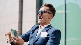 Молодой счастливый бизнесмен идя и разбрасывает доллары на улице около центра офиса, замедленного движения европейское падая небо видеоматериал