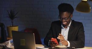 Молодой счастливый бизнесмен имея видеоконференцию через его смартфон на его офисе стола вечером Говорить важный видеоматериал