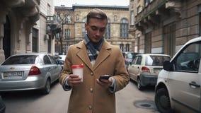 Молодой счастливый бизнесмен используя smartphone и идти с чашкой в улице сток-видео