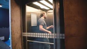 Молодой счастливый вскользь человек ехать прозрачный стеклянный лифт, дверь раскрывает и он идет вне используя smartphone ходя по акции видеоматериалы