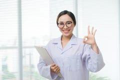 Молодой счастливый жизнерадостный доктор в белой форме показывать о'кеы устно стоковое изображение rf