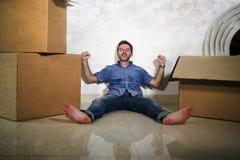 Молодой счастливый и возбужденный пол человека дома наслаждаясь распаковывающ картонные коробки двигая самостоятельно к новый усм стоковые фото
