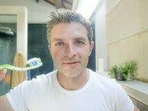 Молодой счастливый и привлекательный белый человек с зубом ванной комнаты голубых глазов дома чистя щеткой с зубной щеткой усмеха стоковые изображения rf