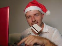 Молодой счастливый и привлекательный человек в шляпе Санта Klaus используя кредитную карточку и ноутбуке для покупки онлайн подар стоковое изображение rf