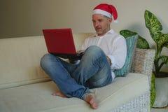 Молодой счастливый и привлекательный человек в шляпе Санта Klaus используя кредитную карточку и ноутбуке для покупки онлайн подар стоковые фото
