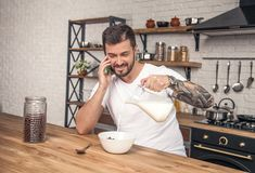 Молодой счастливый красивый усмехаясь парень подготавливает его завтрак на хлопьях кухни смешивая с молоком и имеет телефонный ра стоковое изображение