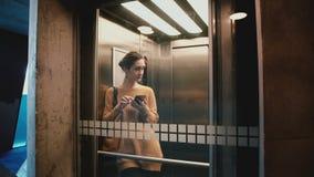 Молодой счастливый лифт катания женщины с стеклянной стеной, дверью раскрывает и она идет вне используя smartphone передвижной хо акции видеоматериалы