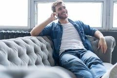 Молодой счастливый ослабленный сидеть человека на софе и говорить на телефоне стоковое фото