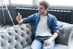 Молодой счастливый ослабленный сидеть человека на софе и говорить на телефоне стоковые фото