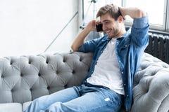 Молодой счастливый ослабленный сидеть человека на софе и говорить на телефоне стоковые изображения