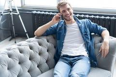 Молодой счастливый ослабленный сидеть человека на софе и говорить на телефоне стоковые фотографии rf