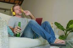 Молодой счастливый расслабленный и привлекательный человек сидя дома кресло софы при шлемофон и компьтер-книжка слушая к музыке и стоковая фотография