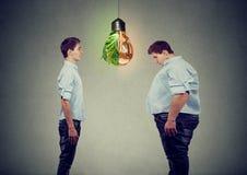 Молодой счастливый тонкий человек смотря унылого тучного парня себя Концепция питания диеты отборная правая стоковые изображения rf