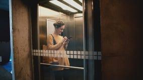 Молодой счастливый усмехаясь лифт катания женщины при прозрачная стеклянная стена, идя вне используя smartphone ходя по магазинам сток-видео
