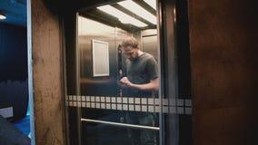 Молодой счастливый человек входит в лифт, нажимает кнопку, дверь закрывает и он едет вверх по использованию мобильного офиса app  акции видеоматериалы