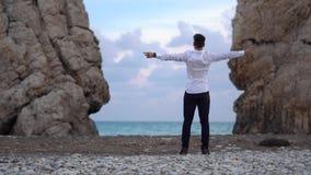 Молодой счастливый человек между 2 горами на взморье с открытыми оружиями enjoing красивая погода Океанские волны побили на утеса акции видеоматериалы