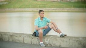 Молодой счастливый человек с smartphone в парке города сидит на береге сток-видео