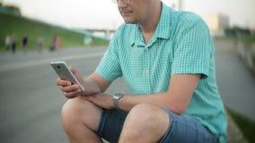 Молодой счастливый человек с smartphone в парке города сидит на береге акции видеоматериалы
