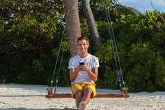 Молодой счастливый человек усаженный на качание и использование его телефона Белые песок и джунгли как предпосылка стоковая фотография