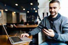 Молодой счастливый человек усмехаясь и держа smartphone сидя с компьтер-книжкой в кафе Человек портрета читая сообщение с smartph стоковое изображение