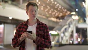 Молодой счастливый человек хипстера думая и используя телефон в городе вечером сток-видео