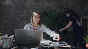 Молодой творческий дизайнер рисующ и пишущ в проекте блокнота превращаясь пока ее коллега распыляет и моет акции видеоматериалы
