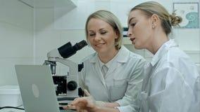 Молодой техник лаборатории 2 с ноутбуком и микроскопом в лаборатории акции видеоматериалы