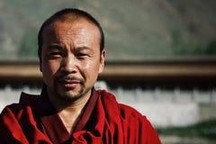 молодой тибетский буддийский монах в красном платье перед его виском монастыря стоковое изображение