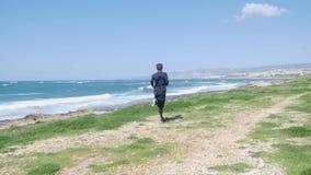 Молодой тонкий кавказский человек бежать на пляже нося черные обмундирование и солнечные очки Волнистое море на предпосылке видеоматериал