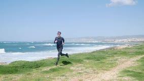 Молодой тонкий кавказский человек бежать на пляже нося черные обмундирование и солнечные очки Ветреный солнечный день ( видеоматериал