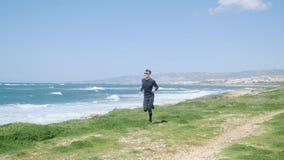 Молодой тонкий кавказский человек бежать на пляже нося черные обмундирование и солнечные очки Ветреный солнечный день видеоматериал