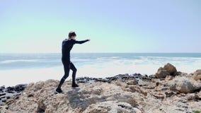 Молодой тонкий подходящий человек кладя воздух в коробку на скалистом пляже Сильные волны ударяют день побережья ветреный солнечн видеоматериал