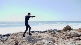 Молодой тонкий подходящий человек кладя воздух в коробку на скалистом пляже Сильные волны ударяют день побережья ветреный солнечн сток-видео