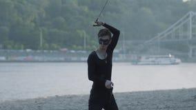 Молодой тонкий человек в черных одеждах и маска выполняя шоу с положением пламени на берег реки береге реки Умелый художник fires акции видеоматериалы