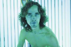 Молодой тонкий человек на солярии в салоне красоты Стоковая Фотография