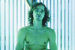 Молодой тонкий человек на солярии в салоне красоты Стоковая Фотография RF